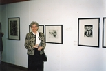 Photograph: Unknown Woman Standing In front of Works by Peter Howson (1993)
