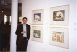 Photograph:Unknown Man Standing With Works at the Opening of 'Breaking the Ice' Exhibition (1992)