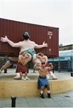 Photograph: Three men posing in front of David Mach sculpture (1994)