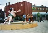 Photograph: Five men pretending to hold up the David Mach sculpture (1994)
