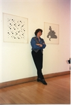 Photograph: Bridget Riley standing with 2 of her works (1996)