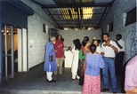 Photograph: Various people milling and talking in the gallery of Art Acre, Calcutta (1998)