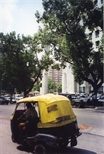 Photograph: A yellow tuk-tuk parked across from several large buildings in India (1998)