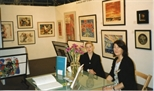 Photograph: Sue Mackechnie and an unknown woman sitting at the desk for Glasgow Print Studio stand at 'Art 97' (1997)