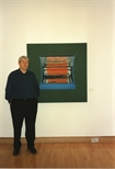 Photograph: Tim Mara standing with his print 'Two Bar Electric Fire II' (1997)