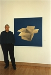 Photograph: A close up view of Tim Mara standing with his print 'Two Bar Electric Fire II' (1997)