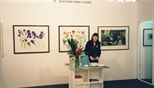 Photograph: Sue MacKechnie standing behind the desk of the Glasgow Print Studio stand at 'Art 97London ' (1997)