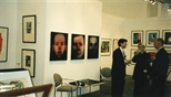 Photograph: John MacKechnie talking with 2 unknown people at the Glasgow Print Studio stand at Art 1997 Chicago (1997)
