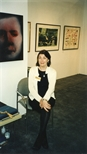Photograph: Sue MacKechnie posing at the Glasgow Print Studio stand at Art 1997 Chicago (1997)