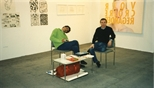 Photograph: 2 men sitting at an unknown stand at Art 1997 Chicago (1997)