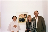 Photograph: Zheng Shuang posing with an unknown couple at the exhibition 'Zheng Shuang Woodcuts 1980-1996' in Glasgow Print Studio Gallery (2000)