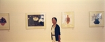 Photograph: Zheng Shuang posing with several of her prints in Glasgow Print Studio Gallery (2000)