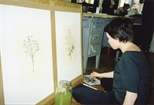 Photograph: A young woman sitting on the floor of Glasgow Print Studio Workshop colouring a print (2002)
