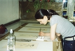 Photograph: A young woman working on several prints in Glasgow Print Studio Workshop (2002)