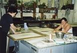 Photograph: 2 young women working on prints in Glasgow Print Studio Workshop (2002)
