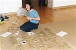 Photograph: Christine Borland in the Glasgow Print Studio Gallery setting up her joint exhibition 'Dragon Doll' with Claire Barclay (2002)