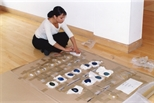 Photograph: An unknown woman unpacking one of Christine Borland's mobile sculptures in Glasgow Print Studio Gallery (2002)
