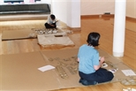 Photograph: Christine Borland and an unknown woman setting up Christine's joint exhibition 'Dragon Doll' with Claire Barclay (2002)